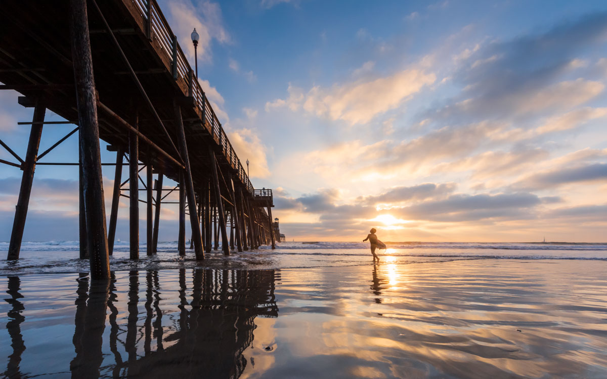 A surfer at the Oceanside Pier at sunset